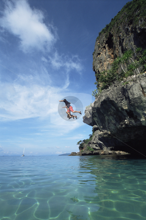 Couple jumping from cliffs into the sea stock photo,  by Monkey Business Images