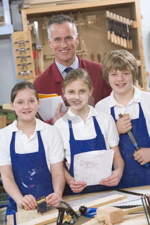 Schoolchildren and teacher in woodwork class stock photo,  by Monkey Business Images