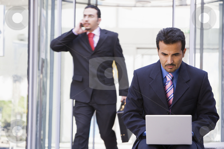 Businessman working at laptop outside  stock photo, Businessman working at laptop outside office by Monkey Business Images