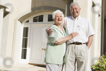 Senior couple standing outside house stock photo, Senior couple standing outside front door of house by Monkey Business Images