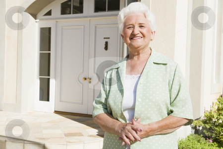 Senior woman standing outside house stock photo, Senior woman standing outside front door of house by Monkey Business Images