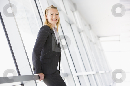 Businesswoman standing in corridor smiling stock photo,  by Monkey Business Images