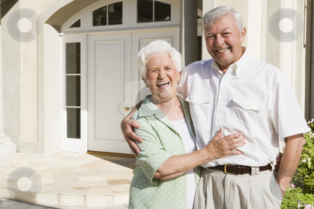 Senior couple standing outside house stock photo, Senior couple embracing outside house by Monkey Business Images