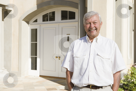 Senior man standing outside house stock photo, Senior man standing outside front door of house by Monkey Business Images