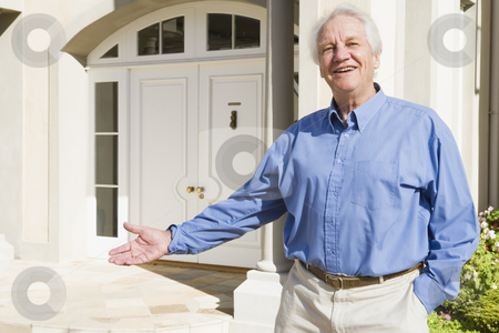 Senior man standing outside house stock photo, Senior man welcoming visitor to home by Monkey Business Images