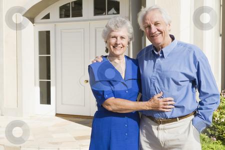 Senior couple outside house stock photo, Senior couple standing outside house by Monkey Business Images