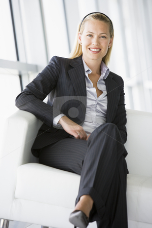 Businesswoman sitting in office lobby smiling stock photo,  by Monkey Business Images