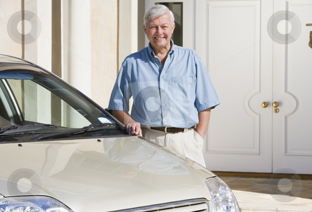 Senior man standing next to new car stock photo, Senior man standing next to new car outside house by Monkey Business Images