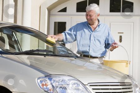 Senior man washing car stock photo, Senior man wasing car with sponge outside house by Monkey Business Images