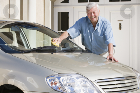 Senior man cleaning car stock photo, Senior man cleaning car outside house by Monkey Business Images
