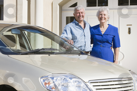 Senior couple standing to new car stock photo, Senior couple standing next to new car outside house by Monkey Business Images
