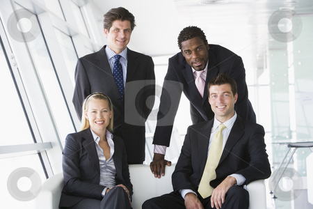 Four businesspeople in office lobby smiling stock photo,  by Monkey Business Images