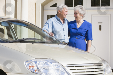Senior couple standing next to car stock photo, Senior couple standing next to car outside house by Monkey Business Images
