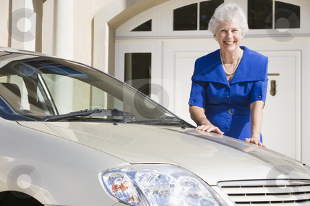 Senior woman standing next to new car stock photo, Senior woman standing next to new car outside house by Monkey Business Images