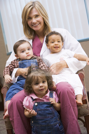 Consultant with three IVF toddlers stock photo, Consultant holding three IVF conceived children by Monkey Business Images