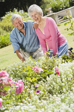 Senior couple working in garden stock photo, Senior couple working in garden flowerbed by Monkey Business Images