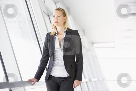 Businesswoman standing in corridor stock photo,  by Monkey Business Images