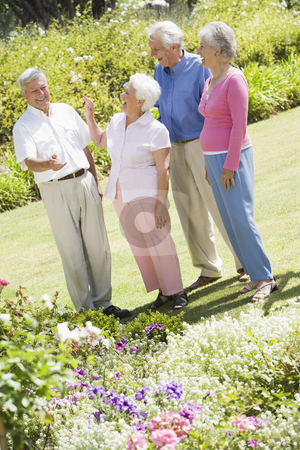 Group of senior friends in garden stock photo, Group of senior friends in garden admiring flowerbeds by Monkey Business Images
