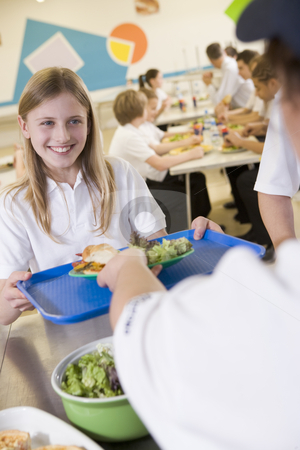 A student collecting lunch from the school cafeteria stock photo,  by Monkey Business Images