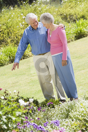 Senior couple in garden stock photo, Senior couple in garden admiring flowerbed by Monkey Business Images