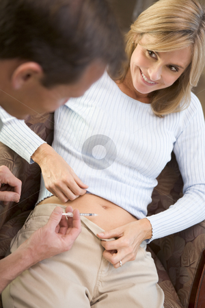 Man helping woman inject drugs to gain pregnancy stock photo, Man helping woman inject drugs to gain pregnancy at home by Monkey Business Images