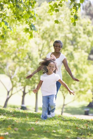 Grandmother and granddaughter running in park and smiling stock photo,  by Monkey Business Images