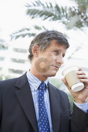 Businessman outdoors drinking coffee stock photo,  by Monkey Business Images