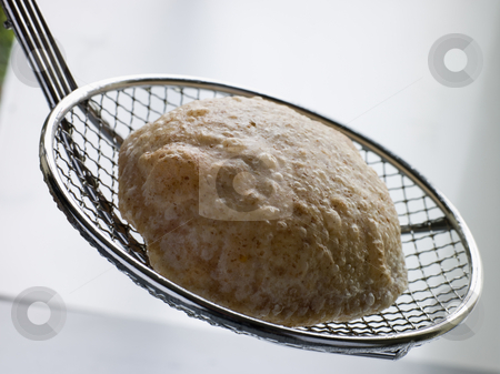 Deep Fried Puff Bread on a Strainer stock photo, Close up of Deep Fried Puff Bread on a Strainer by Monkey Business Images