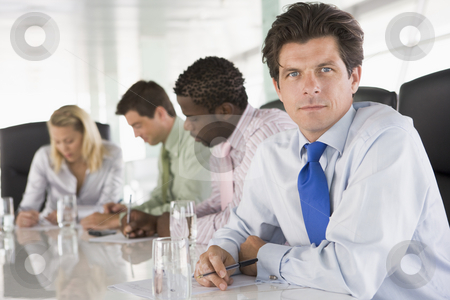 Four businesspeople in a boardroom writing stock photo,  by Monkey Business Images