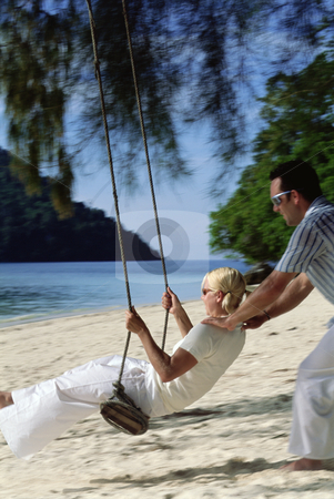 Man swinging woman on swing at beach,  stock photo,  by Monkey Business Images