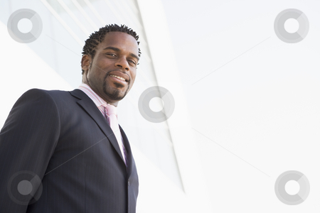 Businessman standing outdoors by building smiling stock photo,  by Monkey Business Images