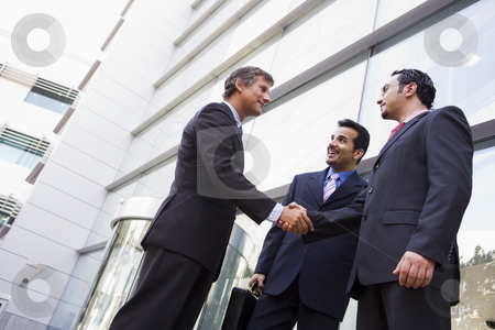 Group of businessmen shaking hands outside office stock photo, Group of businessmen shaking hands outside office building by Monkey Business Images