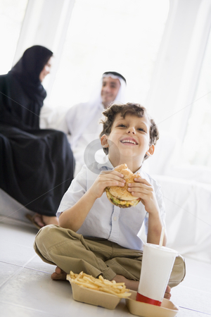A Middle Eastern boy enjoying a fast food burger meal stock photo,  by Monkey Business Images