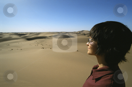 Young woman looking across sand dunes stock photo,  by Monkey Business Images