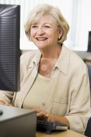 Senior woman working on a computer stock photo,  by Monkey Business Images