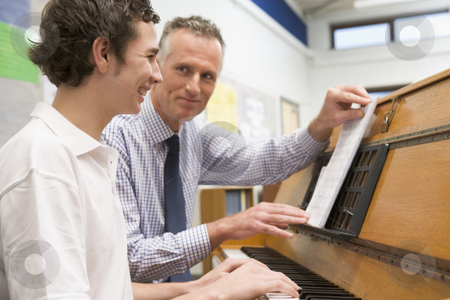 Teacher with schoolboy playing piano in music class stock photo,  by Monkey Business Images
