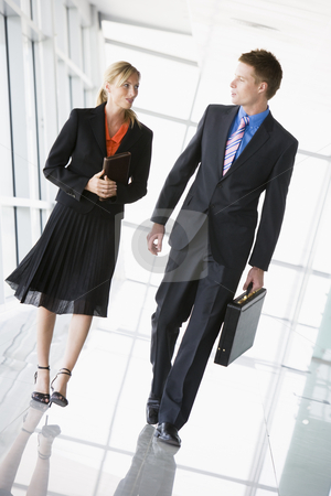 Two businesspeople walking in corridor talking stock photo,  by Monkey Business Images