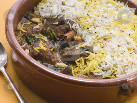 Pot of Lamb Biryani with a spoon stock photo, Close up of Pot of Lamb Biryani with a spoon by Monkey Business Images