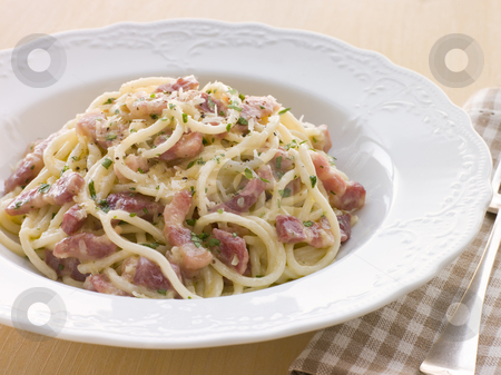 Bowl of Linguini Carbonara stock photo, Bowl of Linguini Carbonara with fork by Monkey Business Images