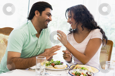 A Middle Eastern couple enjoying a meal together stock photo,  by Monkey Business Images