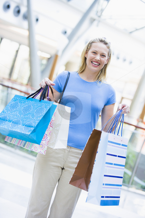 Woman shopping in mall stock photo, Woman shopping in mall carrying bags by Monkey Business Images