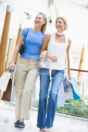 Two friends shopping in mall stock photo, Two friends shopping in mall carrying bags by Monkey Business Images