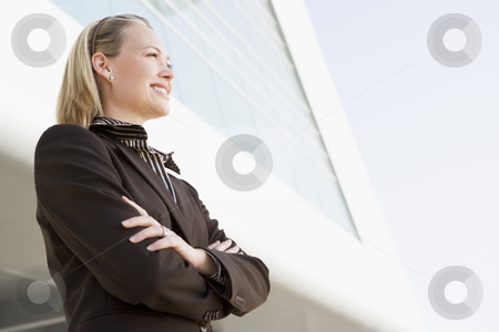 Businesswoman standing outdoors by building smiling stock photo,  by Monkey Business Images