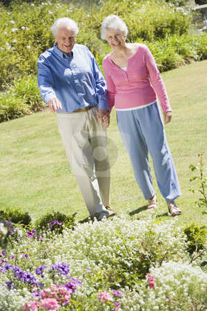 Senior couple walking in garden stock photo, Senior couple walking in garden admiring flowerbeds by Monkey Business Images