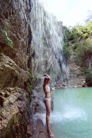 Woman in bikini standing under waterfall stock photo,  by Monkey Business Images