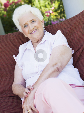 Senior woman sitting on garden chair stock photo, Senior woman sitting on garden chair smiling to camera by Monkey Business Images