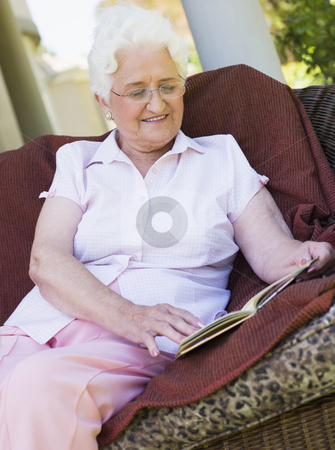 Senior woman reading book  stock photo, Senior woman reading book sitting on garden furniture by Monkey Business Images