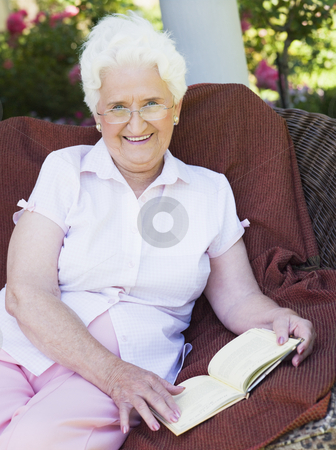 Senior woman reading book stock photo, Senior woman reading book sitting on garden chair by Monkey Business Images