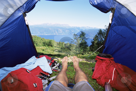 Man lying in tent with a view of lake stock photo,  by Monkey Business Images