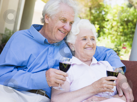 Senior couple relaxing with glass of wine stock photo, Senior couple relaxing with glass of red wine by Monkey Business Images